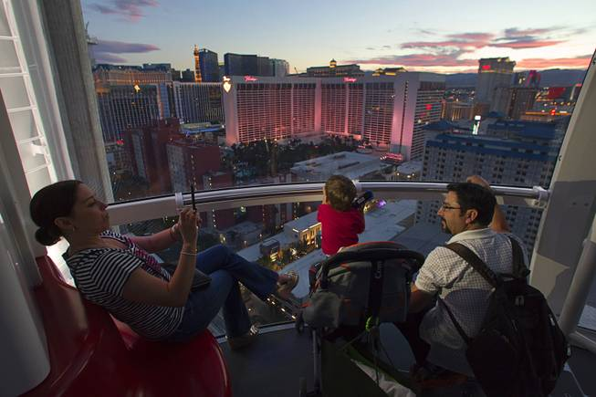 Carolina Higuera of Mexico takes a photo of her son Simon Torres, 20-months, and husband Leoncio Tores while riding the 550 foot-tall High Roller observation wheel, the tallest in the world, Wednesday, April 9, 2014. The wheel is the centerpiece of the $550 million Linq project, a retail, dining and entertainment district by Caesars Entertainment Corp.