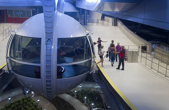 Passengers depart a cabin after riding the 550 foot-tall High Roller observation wheel, the tallest in the world, Wednesday, April 9, 2014. The wheel is the centerpiece of the $550 million Linq project, a retail, dining and entertainment district by Caesars Entertainment Corp.