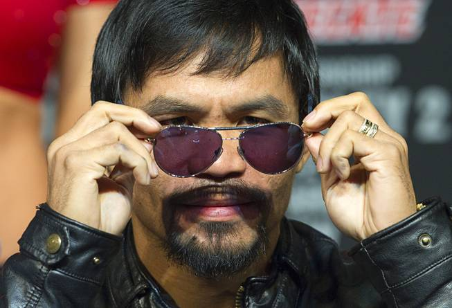 Boxer Manny Pacquiao of the Philippines takes off his sunglasses during a news conference at the MGM Grand Wednesday, April 9, 2014. Pacquiao will challenge undefeated WBO welterweight champion Timothy Bradley at the MGM Grand Garden Arena on Saturday. The fight is a rematch to a June 9, 2012 fight that Bradley won.