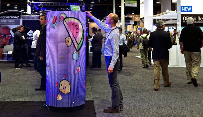A P6 Indoor Cylinder from the DesignLED Technology Co. has a flexible LED screen attracting the curious during the National Association of Broadcasters show at the Las Vegas Convention Center on Tuesday, April 8, 2014.