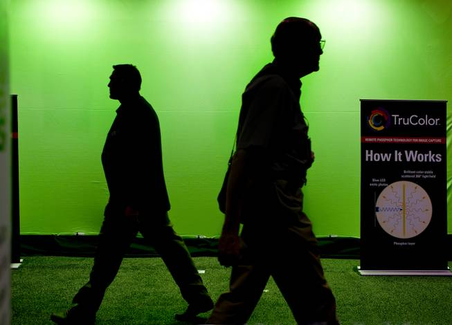 Attendees walk past a green screen offered by TruColor during the National Association of Broadcasters show at the Las Vegas Convention Center on Tuesday, April 8, 2014.