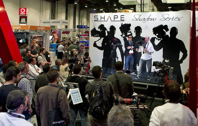 A team from Shape Camera Equipment show off their camera rigs before a large crowd at the National Association of Broadcasters show in the Las Vegas Convention Center on Tuesday, April 8, 2014.