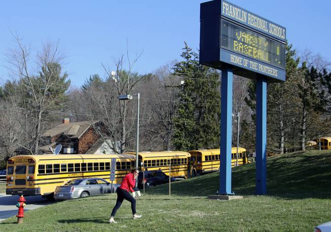A woman walks onto the campus of the Franklin Regional School District where several people were stabbed at Franklin Regional High School on Wednesday, April 9, 2014, in Murrysville, Pa., near Pittsburgh. The suspect, a male student, was taken into custody and being questioned.