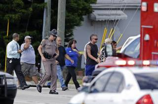 A Florida state trooper, center, escorts a group of parents to a day care center to pick up their children after a vehicle crashed into the center, Wednesday, April 9, 2014, in Winter Park, Fla. At least 15 people were injured, including children.