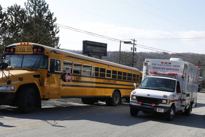 A Salvation Army disaster services vehicle drives past a school bus onto the campus of the Franklin Regional School District where several people were stabbed at Franklin Regional High School, Wednesday, April 9, 2014 in Murrysville, Pa., near Pittsburgh. The suspect, a male student, was taken into custody and being questioned.