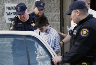 Alex Hribal, center, the suspect in the stabbings at the Franklin Regional High School near Pittsburgh, is taken from a district magistrate after he was arraigned on charges in the attack on Wednesday, April 9, 2014 in Export, Pa. Authorities say Hribal has been charged after allegedly stabbing and slashing at least 19 people, mostly students, in the crowded halls of his suburban Pittsburgh high school Wednesday.