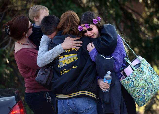 Parents and students embrace along School Road near Franklin Regional High School after more than a dozen students were stabbed by a knife wielding suspect at the school on Wednesday, April 9, 2014, in Murrysville, Pa., near Pittsburgh. The suspect, a male student, was taken into custody and is being questioned.