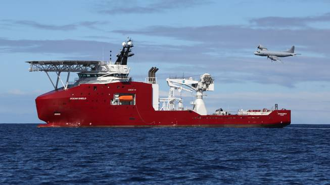 In this April 9, 2014, photo provided by the Australian Defense Force, a Royal Australian Air Force AP-3C Orion flies past Australian Defense vessel Ocean Shield on a mission to drop sonar buoys to assist in the acoustic search of the missing Malaysia Airlines Flight 370 in the southern Indian Ocean.