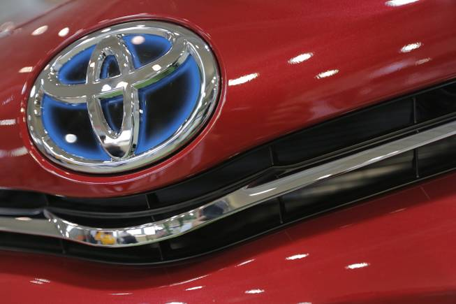 In this Aug. 2, 2013, photo, the emblem of a Toyota car shines at Toyota Motor Corp.'s showroom Toyota Mega Web in Tokyo.