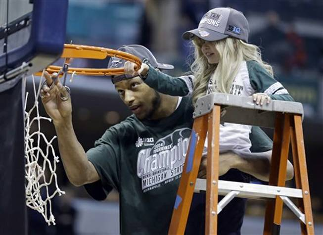 Michigan State forward Adreian Payne, left, cuts the net with Lacey Holsworth, who became close to Payne, after Michigan State defeated Michigan 69-55in the championship of the Big Ten Conference tournament on Sunday, March 16, 2014, in Indianapolis. Holsworth died of cancer on Tuesday, April 8, 2014, her family announced.