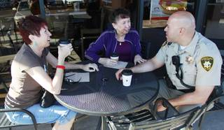 Michelle Bresette, left, and Jan Primavera talk with Metro officer Danny Cordero during a