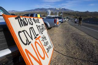 A couple walks past a sign during a protest in support of the Bundy family near Bunkerville Thursday, April 10, 2014.