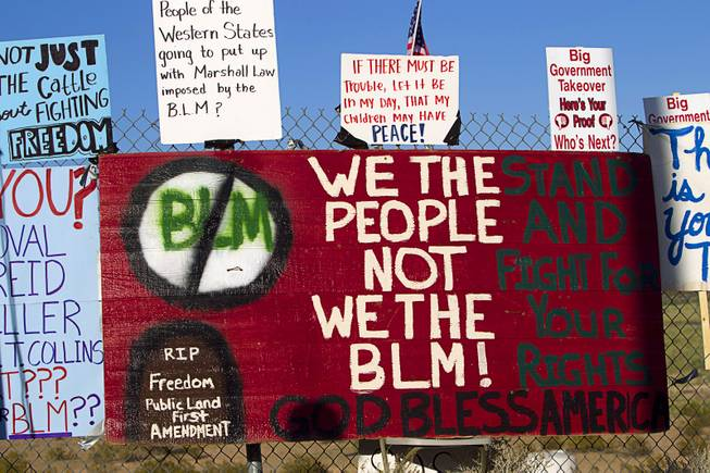 Signs are shown on a fence during a protest in support of the Bundy family Thursday, April 10, 2014, near Bunkerville.