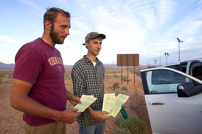 Brothers Tyler Shillig, left , and Spencer Shillig, of St. George, Utah, show their citations after being cited by Bureau of Land Management  officers in the Lake Mead National Recreation Area near Overton Thursday, April 10, 2014.