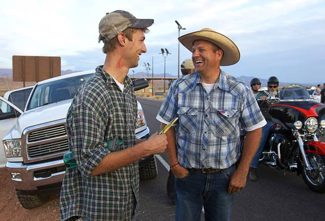 Spencer Shillig, left, of St. George, Utah talks with Ammon Bundy being cited by Bureau of Land Management officers in the Lake Mead National Recreation Area near Overton Thursday, April 10, 2014.