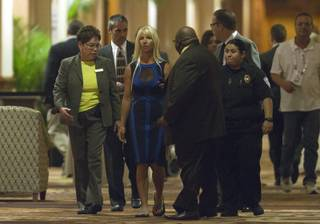 A woman, center, is led away by a security team after an object was thrown at former Secretary of State Hillary Clinton as she spoke to members of the Institute of Scrap Recycling Industries during their annual convention at the Mandalay Bay Convention Center Thursday, April 10, 2014.