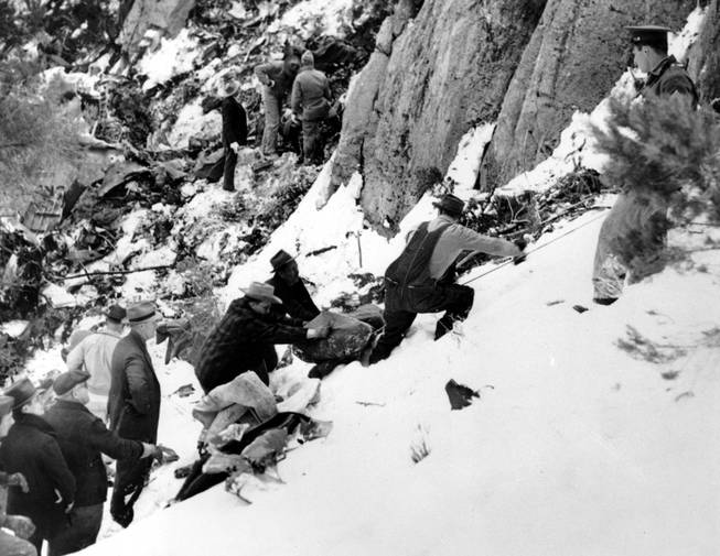 The blanket-wrapped body of film actress Carole Lombard is removed from the shattered wreckage of the Los Angeles bound TWA air liner on Table Mountain, near Las Vegas, Nev., on Jan. 18, 1942.  Lombard, 33, who was on tour to sell war bonds, and 21 other passengers, were killed when the plane crashed into the cliff high on the snow-covered mountain on Jan. 16.  In the background are searchers looking for other bodies.