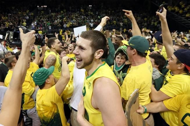 Oregon's Ben Carter, center, celebrates with teammates and fans on the court after the upset 64-57 win over Arizona in an NCAA college basketball game in Eugene, Ore. on Saturday, March 8, 2014.