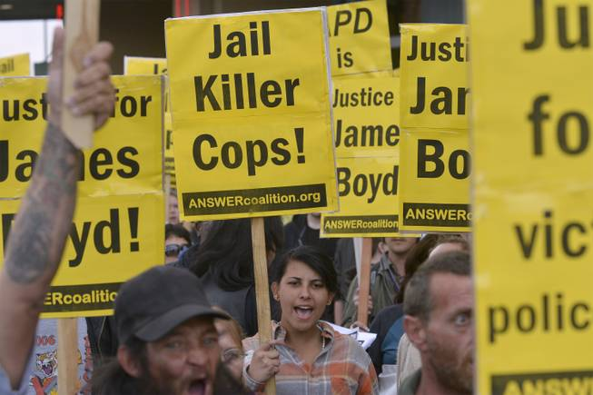 Mariee McCoy, center, of Albuquerque holds up a sign protesting Albuquerque Police Department officers during a protest that started at First and Central and marched to APD headquarters in Albuquerque on Tuesday, March 25, 2013.