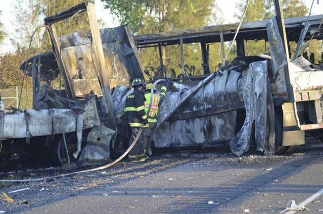 Firefighters hose down the wreckage of a bus and a semitruck that collided, Thursday, April 10, 2014, just north of Orland, Calif., that left at least nine dead.