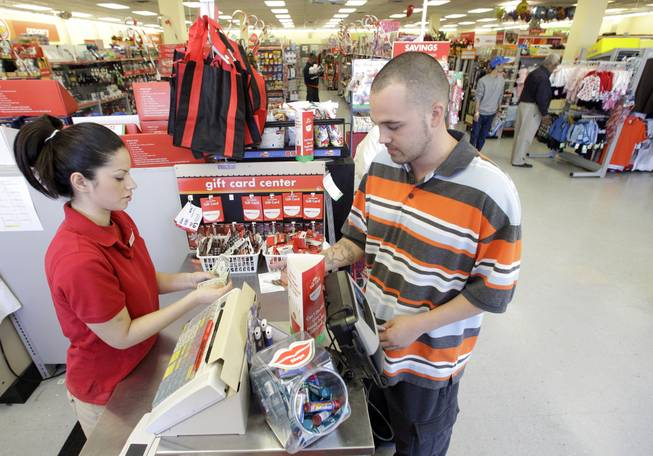 In this photo taken Dec. 14, 2010, Family Dollar employee Pamela Ramos assists John Conner with a purchase at a store in Waco, Texas. Family Dollar on Thursday, April 10, 2014, said it will be cutting jobs and closing about 370 underperforming stores as it looks for ways to improve its financial performance.