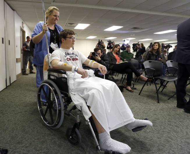 Brett Hurt, a sophomore at Franklin Regional High School in Murrysville, Pa., is wheeled into a news conference by a nurse at Forbes Hospital Thursday, April 10, 2014, in Monroeville, Pa.