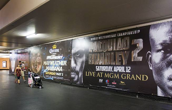 A family passes by advertisements for May 3rd Floyd Mayweather Jr. vs. Marcos Maidana fight and the April 12th Manny Pacquiao vs. Timothy Bradley fight at the MGM Grand Thursday, April 10, 2014. Top Rank CEO Bob Arum, promoter for boxer Manny Pacquiao, voiced his displeasure at the Mayweather signage during a news conference on Wednesday.