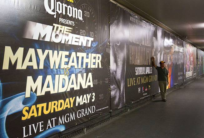 A fan poses by advertisements for May 3rd Floyd Mayweather Jr. vs. Marcos Maidana fight and the April 12th Manny Pacquiao vs. Timothy Bradley fight at the MGM Grand Thursday, April 10, 2014. Top Rank CEO Bob Arum, promoter for boxer Manny Pacquiao, voiced his displeasure at the Mayweather signage during a news conference on Wednesday.