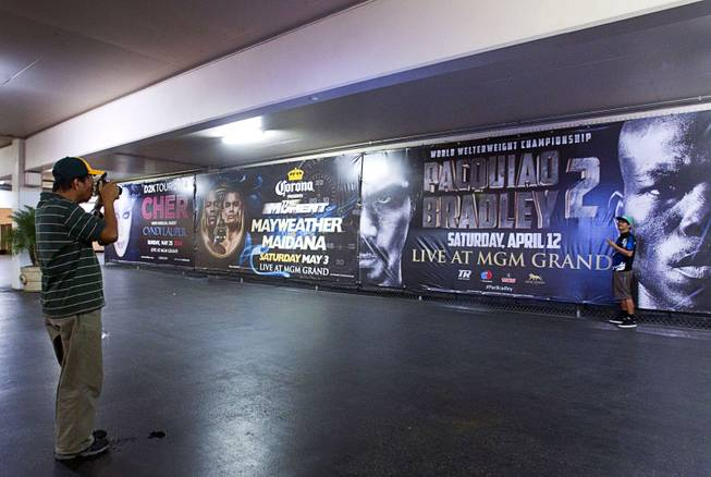 A fan has his photo taken by advertisements for May 3rd Floyd Mayweather Jr. vs. Marcos Maidana fight and the April 12th Manny Pacquiao vs. Timothy Bradley fight at the MGM Grand Thursday, April 10, 2014. Top Rank CEO Bob Arum, promoter for boxer Manny Pacquiao, voiced his displeasure at the Mayweather signage during a news conference on Wednesday.