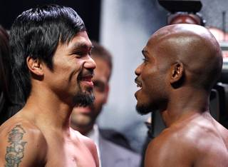Boxer Manny Pacquiao, left, of the Philippines and undefeated WBO welterweight champion Timothy Bradley face off during an official weigh-in at the MGM Grand Garden Arena Friday, April 11, 2014. Pacquiao will challenge Bradley at the arena on Saturday. The fight is a rematch to a June 9, 2012 fight that Bradley won.