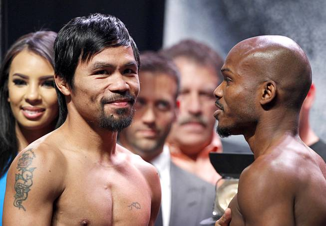 Boxer Manny Pacquiao, left, of the Philippines poses with undefeated WBO welterweight champion Timothy Bradley during an official weigh-in at the MGM Grand Garden Arena Friday, April 11, 2014. Pacquiao will challenge Bradley at the arena on Saturday. The fight is a rematch to a June 9, 2012 fight that Bradley won.