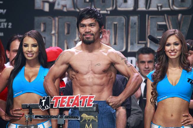 Boxer Manny Pacquiao of the Philippines shows off his physique during an official weigh-in at the MGM Grand Garden Arena Friday, April 11, 2014. Pacquiao will challenge undefeated WBO welterweight champion Timothy Bradley at the arena on Saturday. The fight is a rematch to a June 9, 2012 fight that Bradley won.