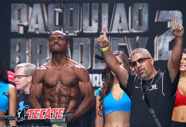 Undefeated WBO welterweight champion Timothy Bradley shows off his physique during an official weigh-in at the MGM Grand Garden Arena Friday, April 11, 2014. His trainer Joel Diaz is at right. Bradley will defend his title against Manny Pacquiao of the Philippines at the arena on Saturday. The fight is a rematch to a June 9, 2012 fight that Bradley won.