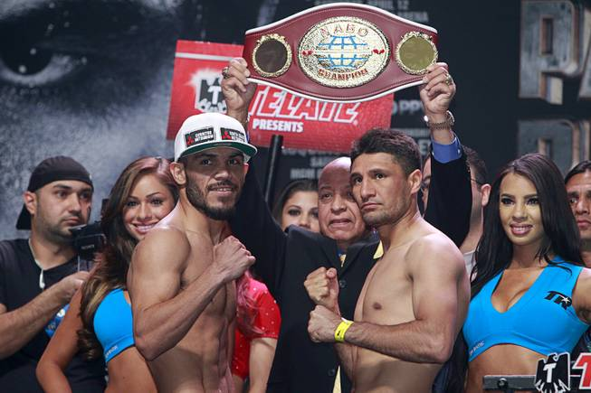 Super featherweight boxers Raymundo Beltran, left, of Mexico and Arash Usmanee of Canada (originally Afghanistan) pose during an official weigh-in at the MGM Grand Garden Arena Friday, April 11, 2014. The boxers will fight in a 10-round lightweight bout.