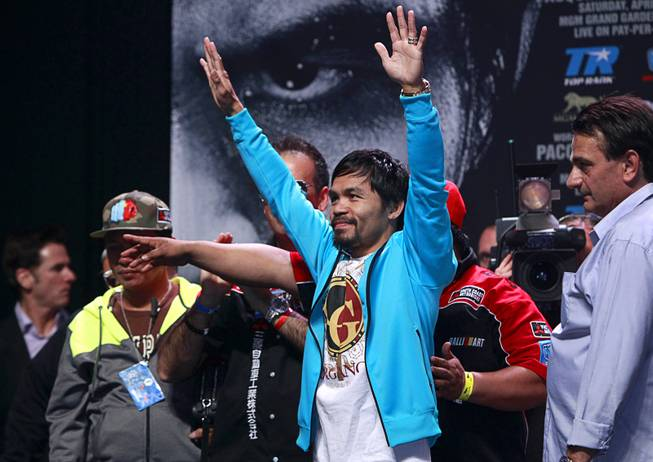 Boxer Manny Pacquiao of the Philippines acknowledges cheers from his fans during an official weigh-in at the MGM Grand Garden Arena Friday, April 11, 2014. Pacquiao will challenge undefeated WBO welterweight champion Timothy Bradley at the arena on Saturday. The fight is a rematch to a June 9, 2012 fight that Bradley won.