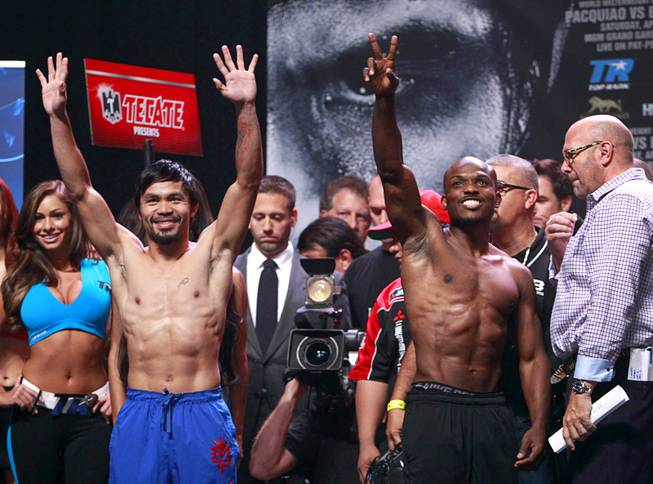 Boxer Manny Pacquiao, left, of the Philippines and undefeated WBO welterweight champion Timothy Bradley wave to fans during an official weigh-in at the MGM Grand Garden Arena Friday, April 11, 2014. Pacquiao will challenge Bradley at the arena on Saturday. The fight is a rematch to a June 9, 2012 fight that Bradley won.