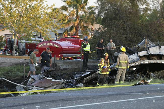 Emergency crews look over wreckage from a crash between a semi and a tour bus on Thursday, April 10, 2014, on Interstate 5 near Orland, Calif.