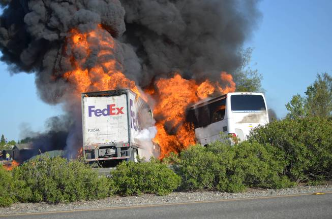 Massive flames are seen devouring both vehicles just after the crash, and clouds of smoke billowed into the sky Thursday April 10, 2014, until firefighters had quenched the fire, leaving behind scorched black hulks of metal. The FedEx tractor-trailer crossed a grassy freeway median in Northern California and slammed into the bus carrying high school students on a visit to a college.