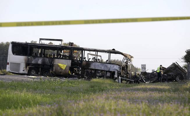 A California Highway Patrol Officer looks over the demolished cab of FedEx truck that crashed into a tour bus, at left, on Interstate 5 Thursday in Orland, Calif., Friday, April 11, 2014. At least ten people were killed and dozens injured in the fiery crash between the truck and a bus carrying high school students on a visit to a Northern California College.