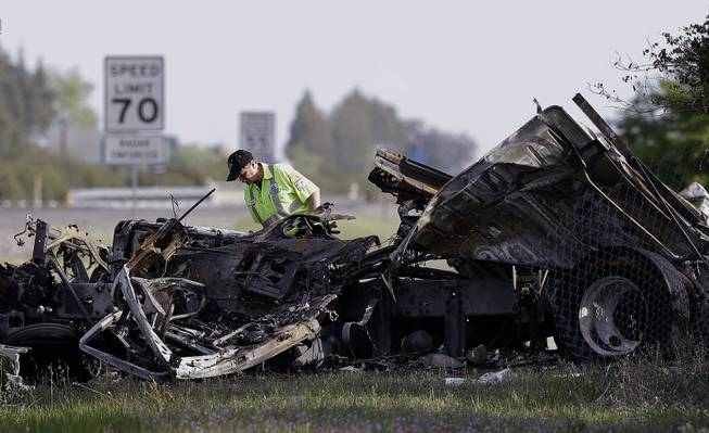 A worker looks over the demolished cab of FedEx truck that crashed into a tour bus on Interstate 5 Thursday in Orland, Calif., Friday, April 11, 2014. At least ten people were killed and dozens injured in the fiery crash between the truck and a bus carrying high school students on a visit to a Northern California College.