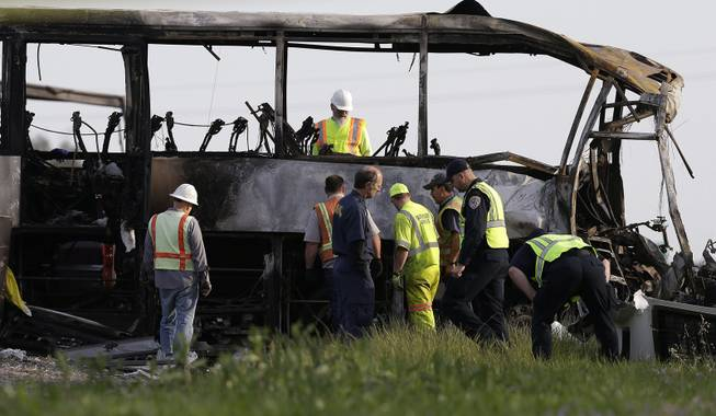 Officials and California Highway Patrol Officers look over the remains of a tour bus that was struck by a FedEx truck on Interstate 5 Thursday in Orland, Calif., Friday, April 11, 2014. At least ten people were killed and dozens injured in the fiery crash between the truck and a bus carrying high school students on a visit to a Northern California College.