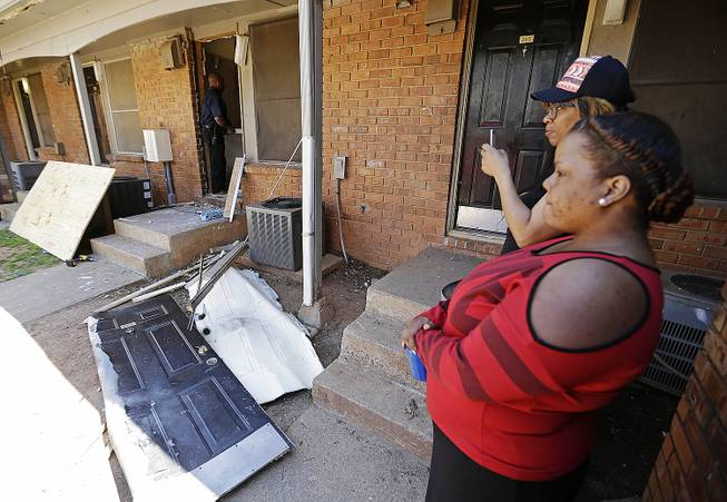 Residents look on as workers repair a neighbor's front door, center, at an apartment complex in Atlanta, Thursday morning, April 10, 2014, where federal agents rescued Frank Arthur Janssen, of Wake Forest, N.C.