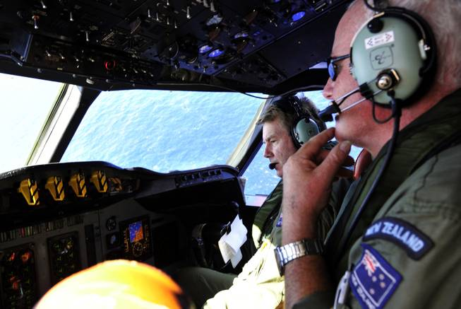 Royal New Zealand Air Force co-pilot and squadron leader Brett McKenzie, left, and flight engineer Trent Wyatt sit in the cockpit aboard a P-3 Orion en route to search the southern Indian Ocean for missing Malaysia Airlines Flight 370, Friday, April 11, 2014.