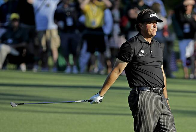 Phil Mickelson reacts after putting his third shot into the water on the 15th hole during the first round of the Masters golf tournament Thursday, April 10, 2014, in Augusta, Ga.