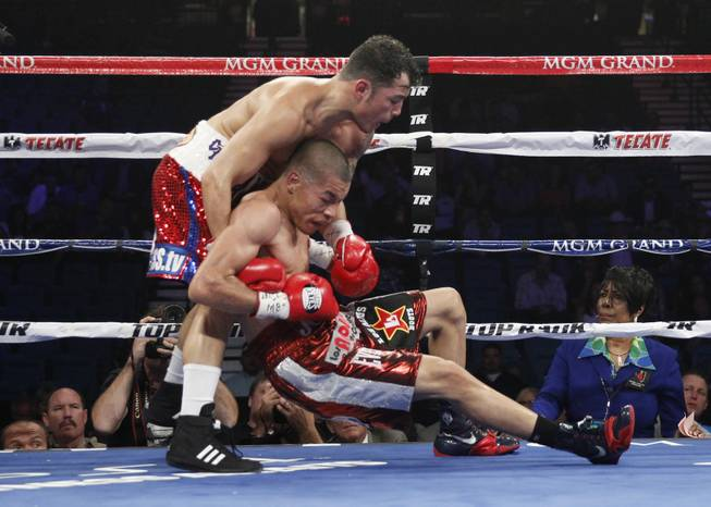Bryan Vazquez grabs Jose Felix as Felix slips to the canvas during their WBA interim super featherweight fight at the MGM Grand Garden Arena on Saturday, April 12, 2014.