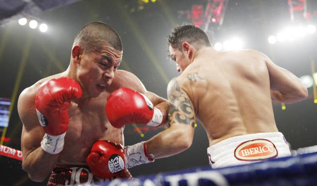 Jose Felix gets hit with a body shot by Bryan Vazquez during their WBA interim super featherweight fight at the MGM Grand Garden Arena on Saturday, April 12, 2014.