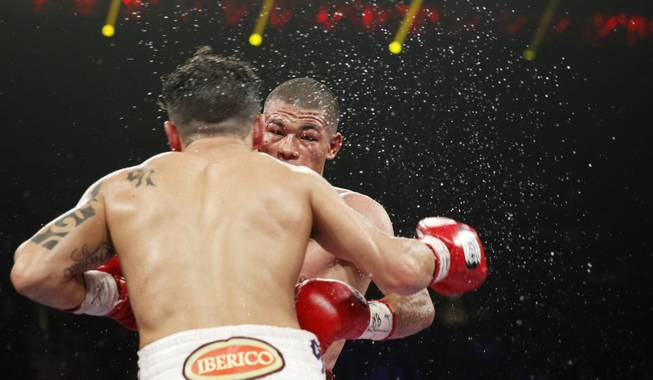 Sweat flies as Bryan Vasquez, left, and Jose Felix trade punches during their WBA interim super featherweight fight at the MGM Grand Garden Arena on Saturday, April 12, 2014.