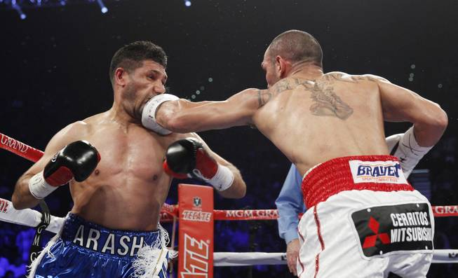 Arash Usmanee, left, is hit with a left from Ray Beltran during a 10-round lightweight fight at the MGM Grand Garden Arena on Saturday, April 12, 2014.