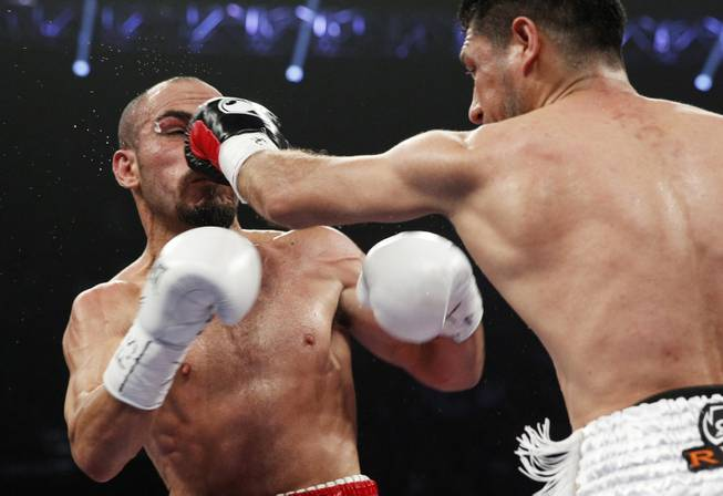 Arash Usmanee, right, hits Ray Beltran with a left during a 10-round lightweight fight at the MGM Grand Garden Arena on Saturday, April 12, 2014.