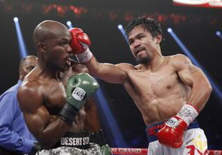 Manny Pacquiao hits undefeated WBO welterweight champion Timothy Bradley with a right during their title fight at the MGM Grand Garden Arena on Saturday, April 12, 2014.